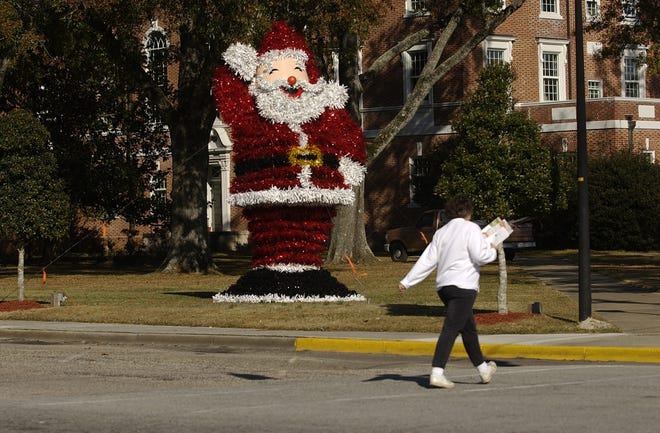 A pedestrian walks past an oversized Santa in the town Square in Burgaw.
