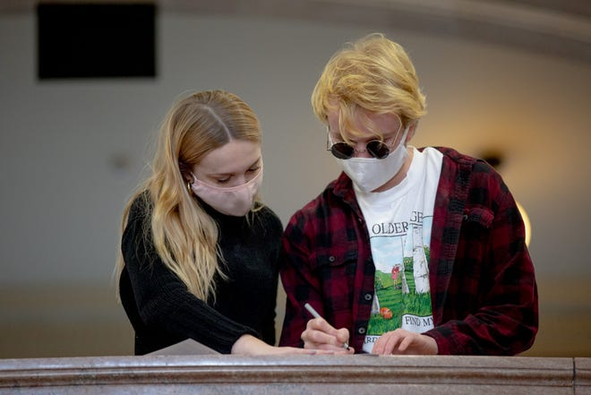 "Maddy Foster, 19, left, and Scott Alexander, 19, who both go to Trinity College, register to vote on Tuesday, Nov. 3, 2020 at the Hartford City Hall. They voted for the first time for a presidential election. ""I decided to register in Connecticut to vote in person to get that in-person voting experience,"" Foster said. ""I'm worried for women's right, which I haven't really thought about until this current election."" They said all of their friends voted and have been talking about the election all day."