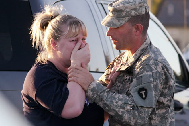 Sgt. Anthony Sills, right, comforts his wife as they wait outside the Fort Hood Army Base near Killeen, Texas on Thursday, Nov. 5, 2009. The Sills' 3-year old son is still in daycare on the base, which is in lock-down following a mass shooting earlier in the day.