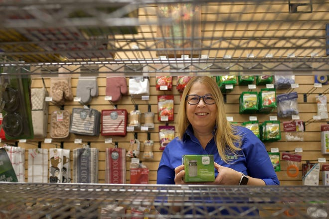 Jessica Bettencourt holds a small canning kit as she stands in front of empty canning shelves at Klem's last week. Bettencourt expects the store will received a new shipment soon.