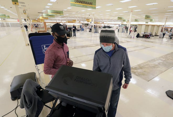 Poll worker Terrence Banks assists Keith Killam with the voting process at the former Shopko store in Neenah. The building served as a consolidated polling place for the city during the coronavirus pandemic.