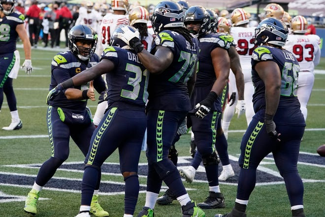 Seattle Seahawks quarterback Russell Wilson, left, greets running back DeeJay Dallas (31), second from left, after Dallas scored a touchdown against the San Francisco 49ers during the second half of an NFL football game, Sunday, Nov. 1.