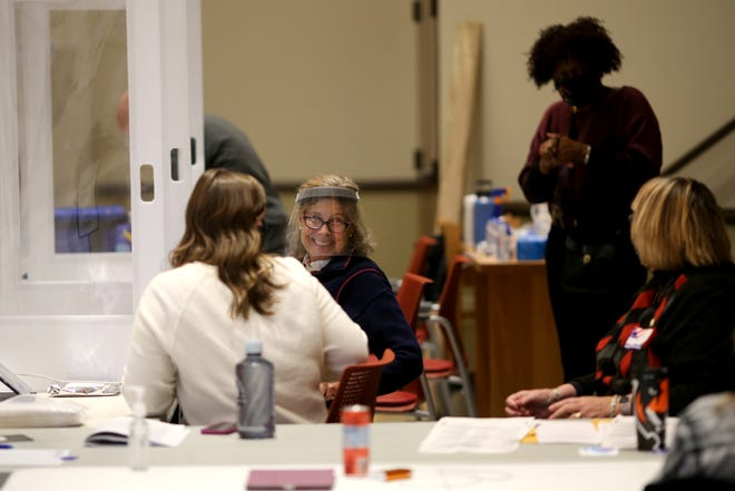 Poll workers share a laugh at the Knox Presbyterian Church polling location, Tuesday, Nov. 3, 2020, in the Hyde Park neighborhood of Cincinnati.