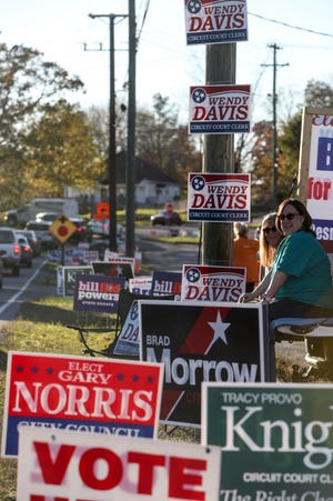 Volunteers waving to passersby sit amongst a sea of campaign signs at the polling location for Election Day at St. Bethlehem Methodist Church in Clarksville, Tenn., on Tuesday, Nov. 3, 2020.