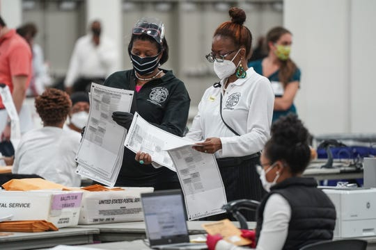 Poll workers count absentee ballots for the city of Detroit at the TCF Center in downtown Detroit on Tuesday, November 3, 2020.