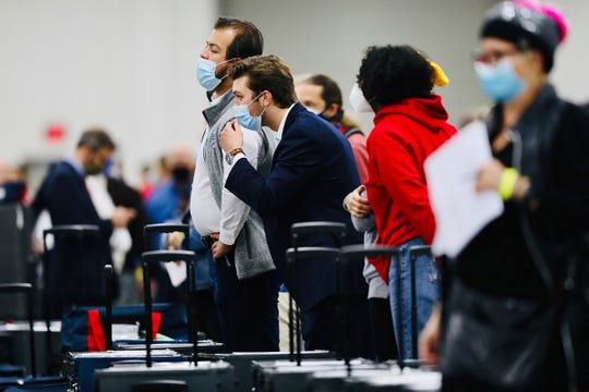 Poll challengers watch the absentee ballots being processed six feet away at the TCF center in Detroit on November 4, 2020.