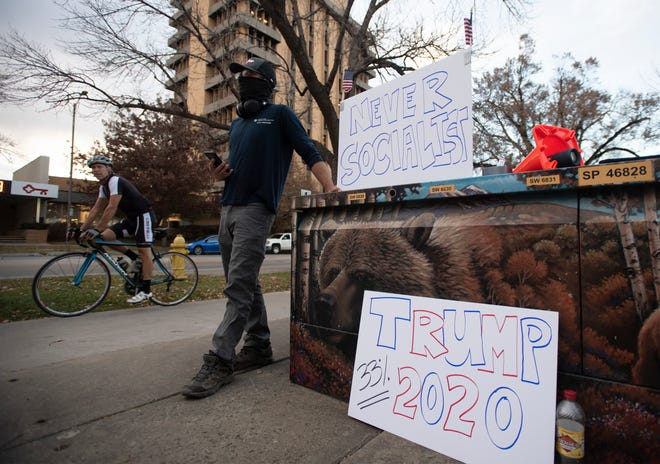 A supporter of U.S. President Donald Trump stands on the sidewalk next to his signs near the Larimer County Courthouse in Fort Collins, Colo. on Tuesday, Nov. 3, 2020.