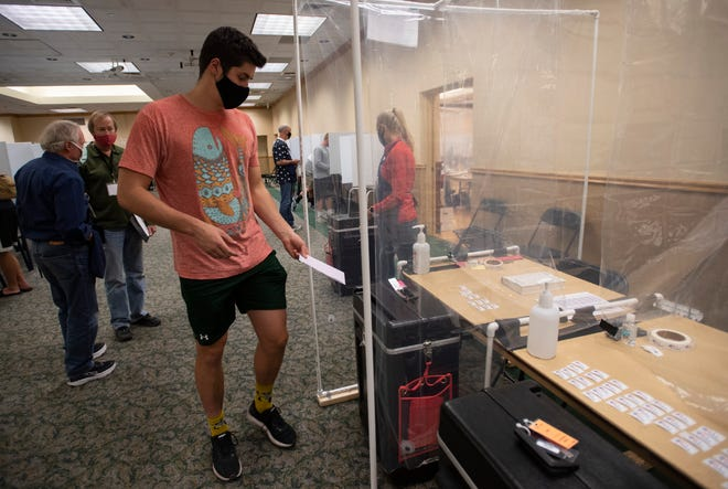 A voter prepares to drop their ballot into the ballot box inside the polling location at Colorado State University in Fort Collins, Colo. on Tuesday, Nov. 3, 2020.