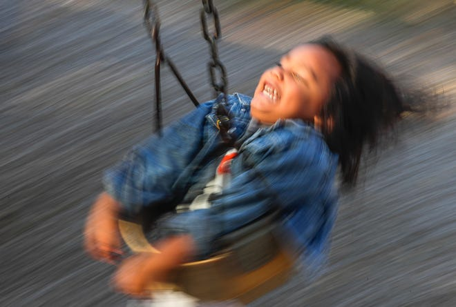 Noah Robinson laughs on a swing set at Joannes Park in Green Bay. The city's parks provide places to be active and create a sense of an inclusive community.