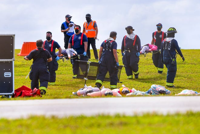 Emergency responders utilize stretchers to move simulated victims from a training area near the runway of the A.B. Won Pat International Airport Authority in Tiyan, Barrigada during a full-scale exercise on Nov. 4, 2020. Personnel from the Airport Firefighters and Police, the Guam Fire Department, and the Guam Police Department, took part in the simulated high activity scenario to test the airport authority's ability to respond to an airport emergency, according to GIAA website.