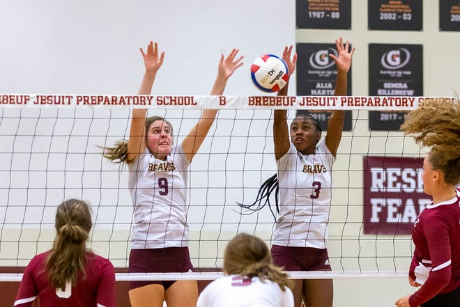 Brebeuf Jesuit middle Greer Fraser (left) and outsider hitter Sydney Robinson (right) go up to make the block.