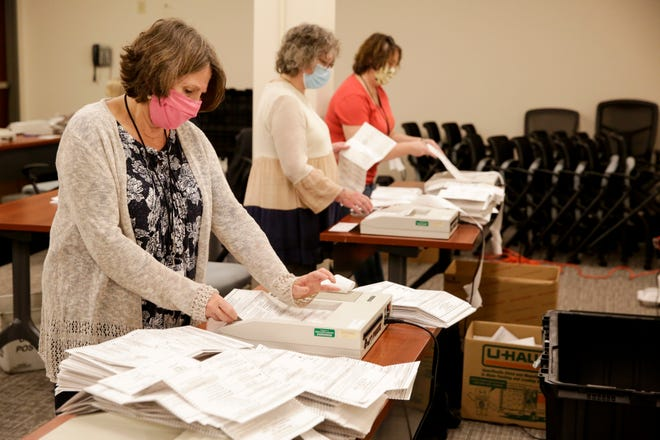 An election workers scans mail-in ballots, Tuesday, Nov. 3, 2020 in Lafayette.