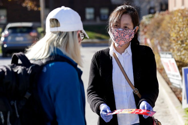 Yue Yin campaigns outside St. Thomas Aquinas Catholic Center, Tuesday, Nov. 3, 2020 in West Lafayette.