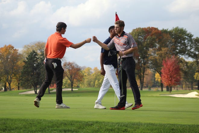 Ashland junior Tyler Sabo, now a two-time All-Ohioan and two-time District Player of the Year, fist bumps his playing partners after the first round of this year's state tournament at The Ohio State University Golf Club.