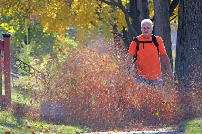 Dan Dahl of Milwaukee blows leaves near his home on North Humboldt Boulevard in Milwaukee on Wednesday. Near-record November warmth will continue for the rest of the week.