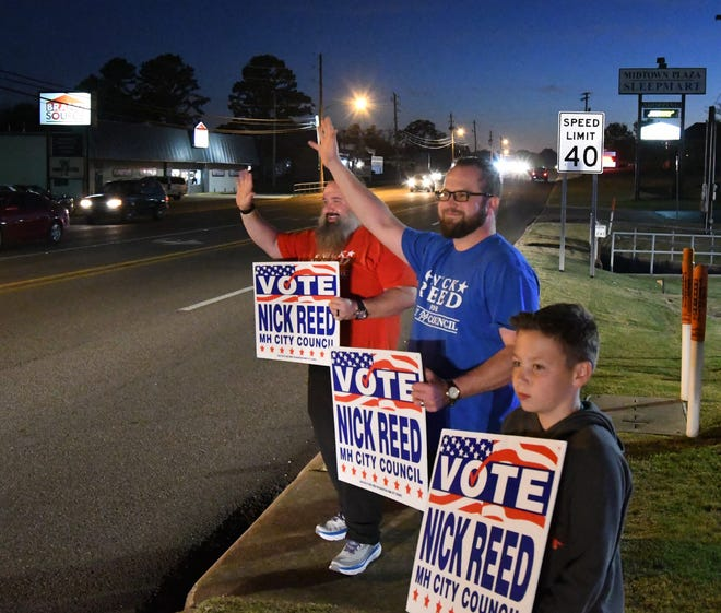 Mountain Home City Council candidate Nick Reed (center) waves at traffic Tuesday night at the corner of Highway 62 East and Wallace Knob Road. Joining Reed are Bob Van Haaren (left) and Keeton Reed (right).