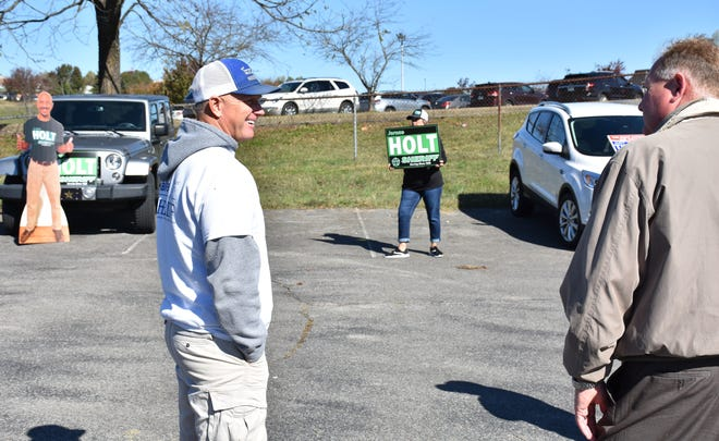 Dickson County sheriff candidates, from left, Kenneth McCallister and Tim Eads talk outside the polling location, with a Jerone Holt cutout in the background, left, at Restoration Church in Dickson on Nov. 3.