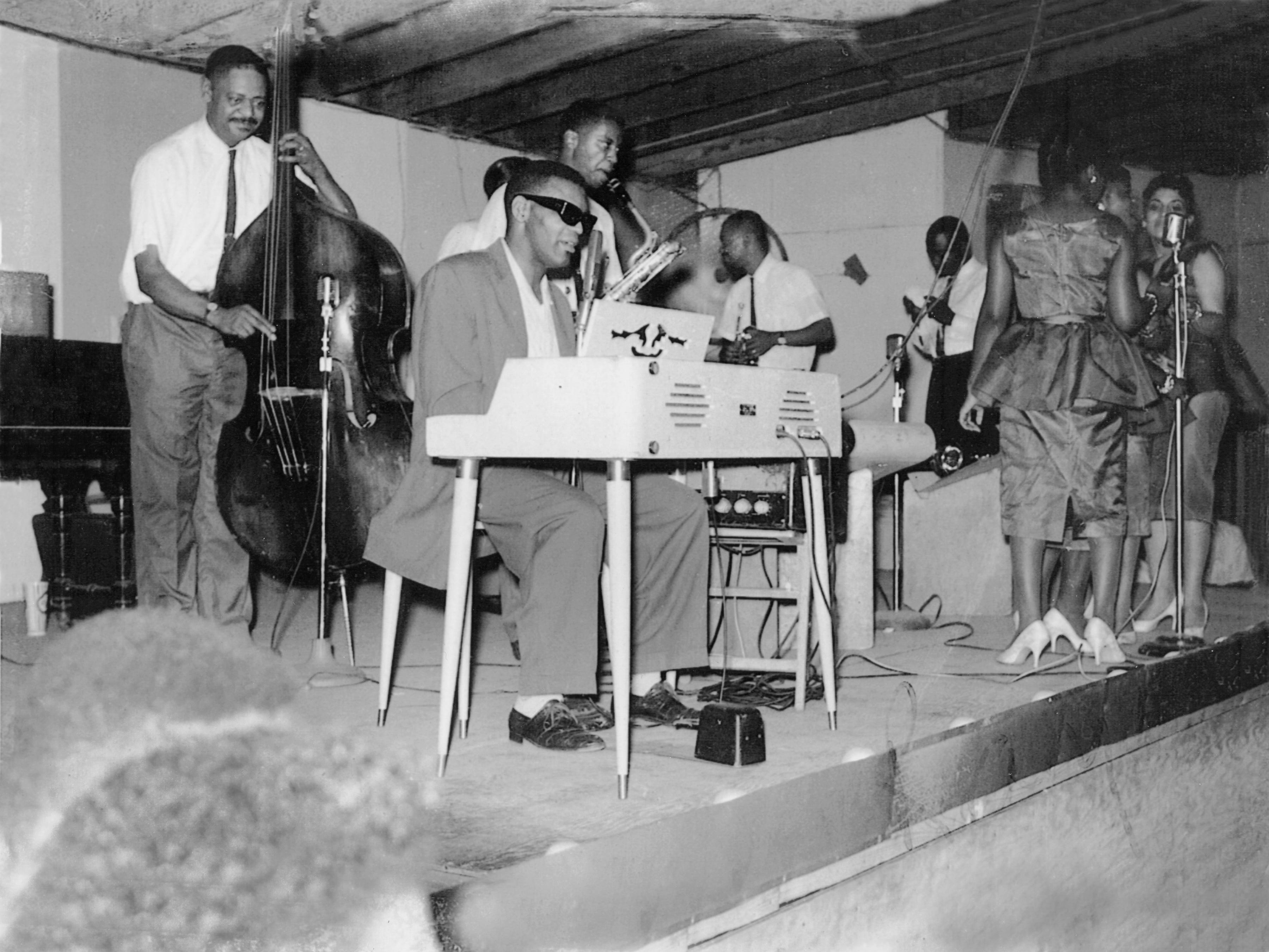 """Ray Charles and band at Maceo's in Nashville, c. 1959. L to R: Edgar Willis, Ray Charles, David """"Fathead"""" Newman, Hank Crawford (looking back), Marcus Belgrave, the Raeletts (Margie Hendrix, Pat Lyles, Gwendolyn Berry, Darlene McCrae)."""