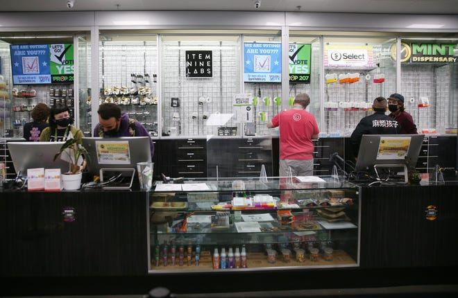Workers work behind a counter at Mint Dispensary in Guadalupe on Nov. 4, 2020. Arizona voters passed Proposition 207, legalizing possession of as much as an ounce of marijuana for adults 21 and older and set up a licensing system for retail sales of the drug.