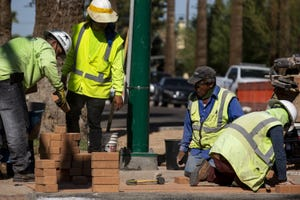 Construction workers lay brick on a sidewalk corner on West Roosevelt Street on Nov. 4, 2020, in downtown Phoenix. Major changes were in store for the weekend, with a nearly 20-degree drop in temperature expected by Saturday.