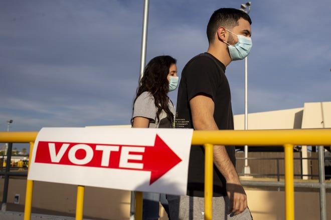 Julissa Barajas and Jesse Ortiz walk together before voting at Arizona Veterans Memorial Coliseum on Nov. 3, 2020, in Phoenix.
