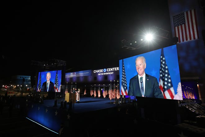 Democratic presidential nominee Joe Biden speaks at a drive-in election night event as Dr. Jill Biden looks on at the Chase Center in in Wilmington, Delaware, early on November 4, 2020. (Win McNamee/Getty Images/TNS)