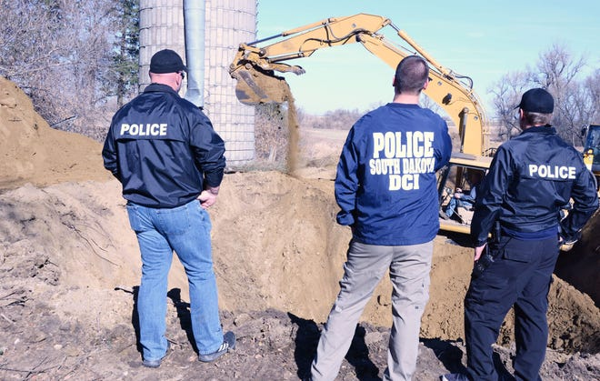 Members of the Watertown Police Department Chad Stahl, left, and Reuben Kinnunen flank Nate Winter of the South Dakota Department of Criminal Investigation while watching a backhoe excavate an old Deuel County well that might contain the remains of Pamela Dunn of Watertown.