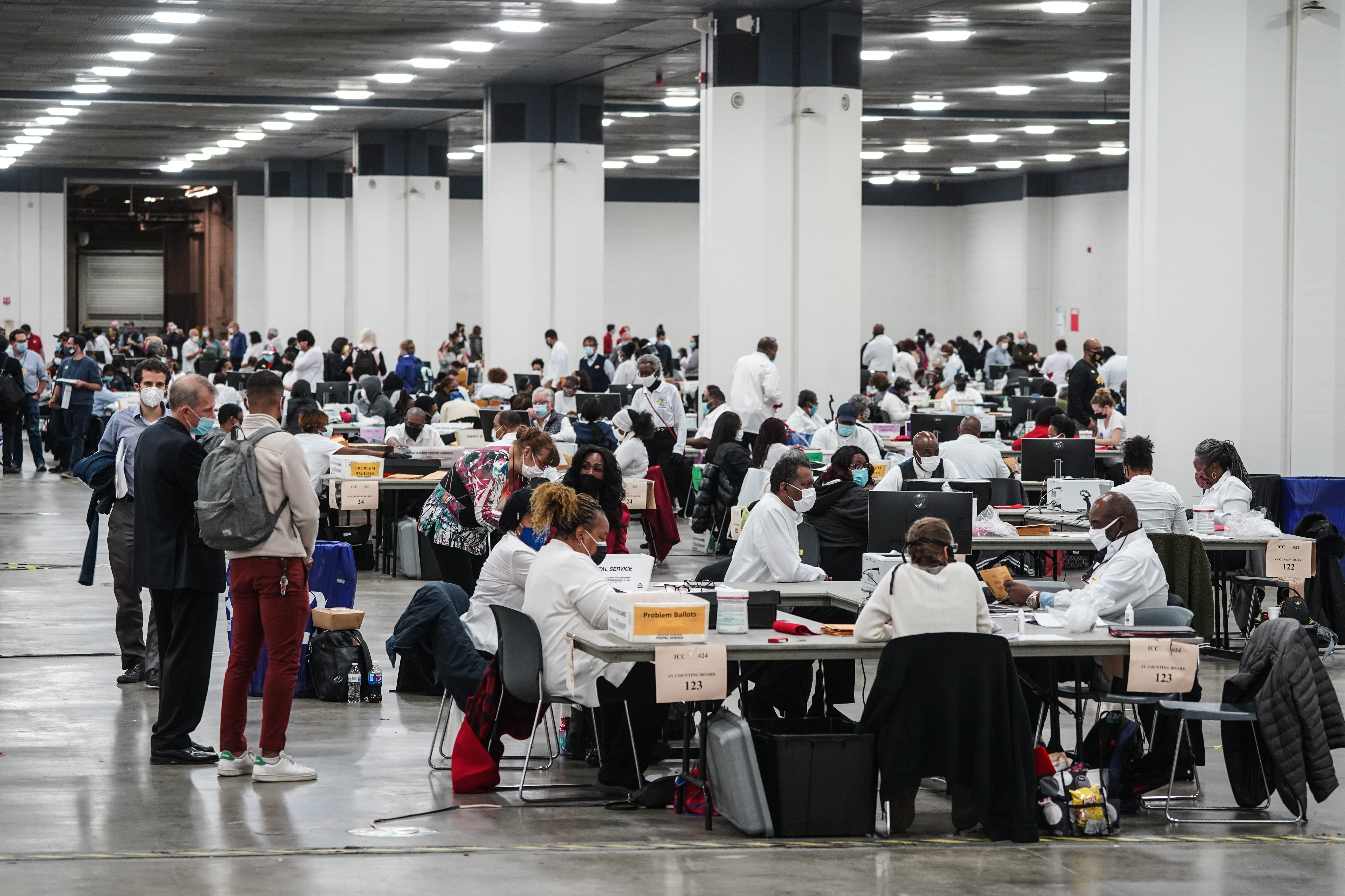 Poll workers count absentee ballots for the city of Detroit at the TCF Center Nov. 3.
