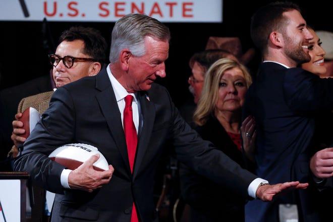 Tommy Tuberville tenía un récord de 159-99 como entrenador en jefe de fútbol americano universitario.  Hizo la pose de Heisman después de pronunciar su discurso de victoria a sus seguidores en su fiesta de observación el 3 de noviembre de 2020 en Montgomery, Alabama.