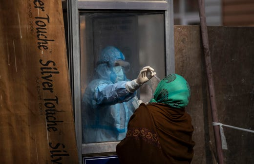 A Kashmiri health worker takes a nasal swab sample to test for COVID-19 in Srinagar, Indian controlled Kashmir, Wednesday, Nov. 4, 2020.