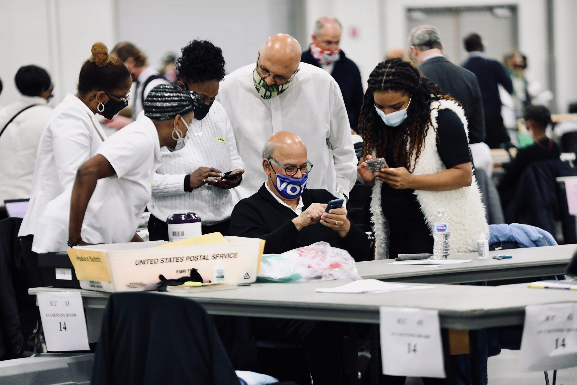 Detroit elections employees examine election results on their phones as they count absentee ballots at the TCF Center on Nov. 4.