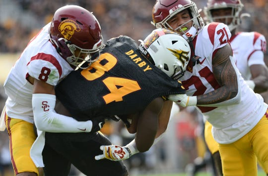 Southern California cornerback Chris Steele (8) and  safety Isaiah Pola-Mao (21) tackle Arizona State wide receiver Frank Darby during their 2019 game at Sun Devil Stadium.
