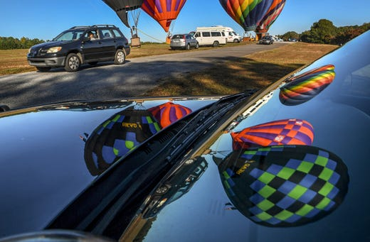 Cars with seniors drive by hot air balloons during the 5th annual Golden Years Jamboree, a drive-through event at the balloon launch field near the Anderson Civic Center  in Anderson, S.C. Wednesday, Nov. 4, 2020. The annual jamboree was originally scheduled for last July, but was postponed as governments responded to the threat of COVID-19 by postponing events, and in many cases cancelling them. The seniors held their event, with over 100 cars with seniors driving through.