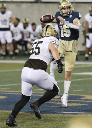 Akron quarterback Zach Gibson leaps to pass as Western Michigan Braden Fiske closes in during Wednesday's game at InfoCision Stadium.