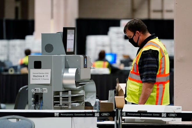 A Philadelphia election worker scans ballots for the 2020 general election Tuesday at the Pennsylvania Convention Center in Philadelphia.