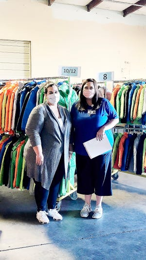 Veronica Ramirez, left, and Misty Wishall stand in front of the 400 coats right before the first night of distribution.