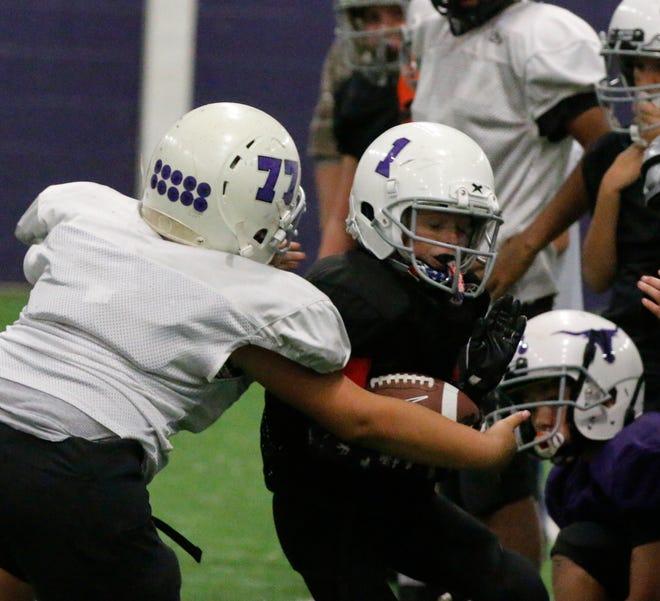 Early Pee Wee Maddox Hair runs toward defender Orlando Mendoza during a tackling drill Tuesday night in Early High School's Big Room. Both boys are fifth-graders.