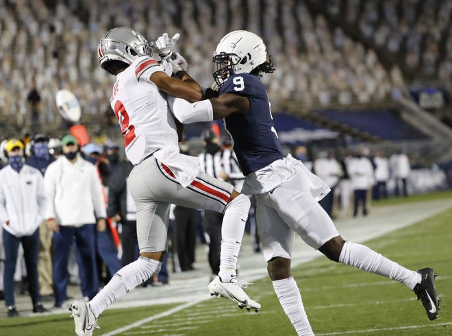 Ohio State's Chris Olave comes down with Justin Fields' pass in the end zone to complete a 26-yard touchdown pass in the first quarter of the Buckeyes' victory last week at Penn State. Joey Porter Jr. is defending.