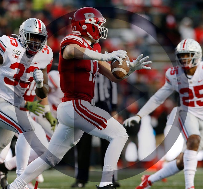 In this file photo, Ohio State Buckeyes defensive end Zach Harrison (33) and safety Brendon White (25) pressure Rutgers Scarlet Knights quarterback Johnny Langan (17) during the second quarter of the NCAA football game at SHI Stadium in Piscataway, N.J. on Saturday, Nov. 16, 2019.