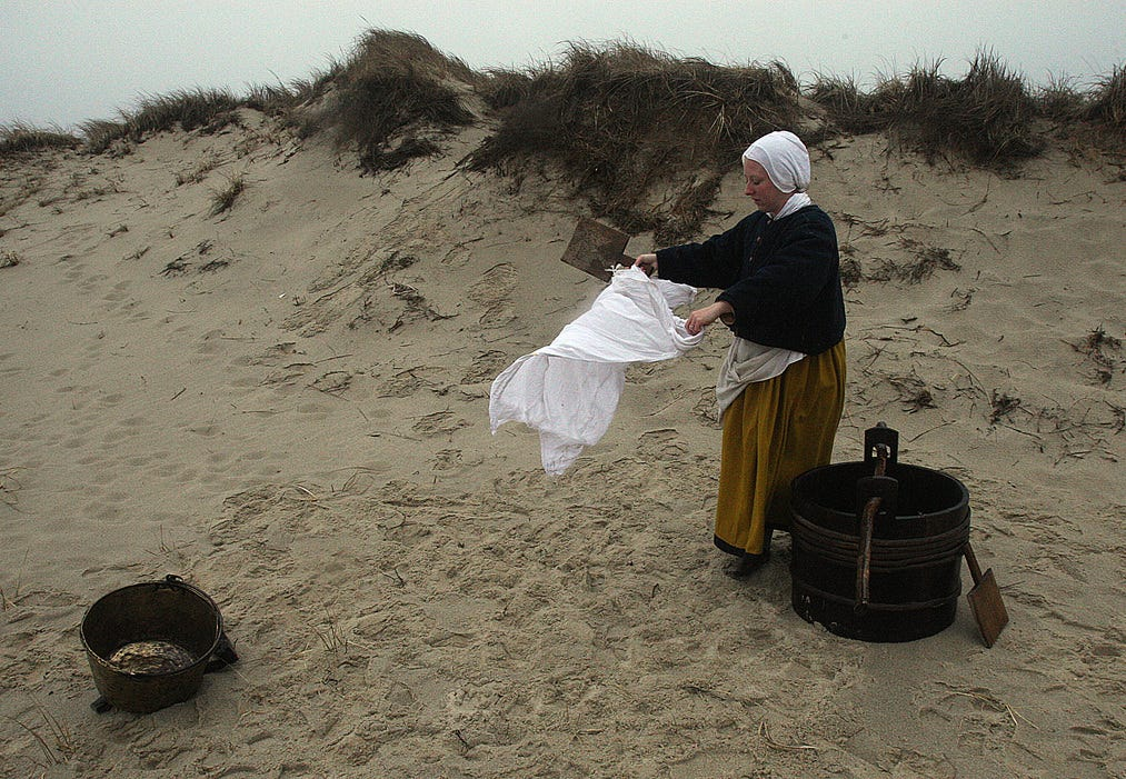 """TRURO--031516-- Plimoth Plantation visits the Cape to study the Pilgrims' three exploratory trips and initial Native/Colonists interactions on their original landscapes. Kristen Haggerty took off her winter jacket and traded it for a Pilgrim outfit and washed clothes, reenacting the """"first washing""""  as part of a surprise for the tour.  Steve Haines/Cape Cod Times"""