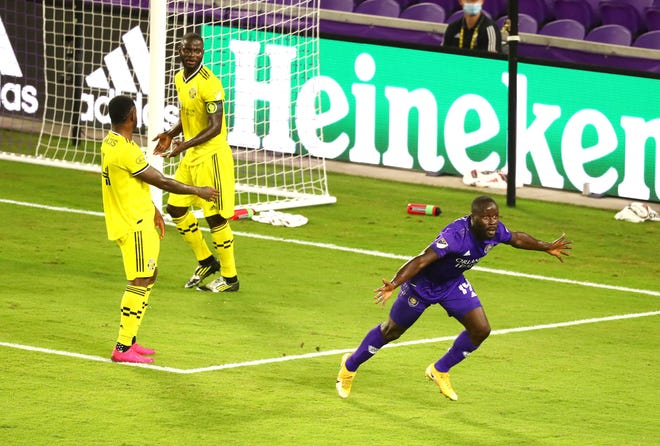Orlando City forward Benji Michel celebrates after scoring the winning goal as the Crew's Waylon Francis, left, and Jonathan Mensah try to figure out how it happened.