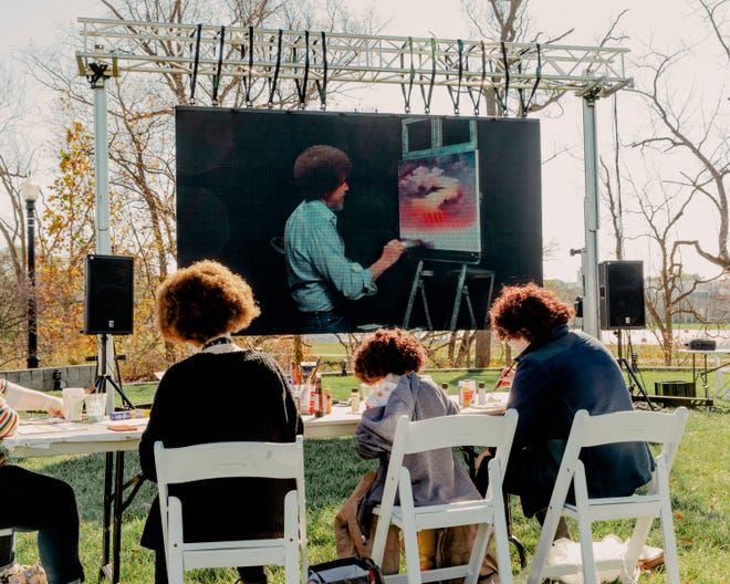 "Fans of Bob Ross try their hand at recreating ""Sunset Aglow"" from a 1993 episode of ""The Joy of Painting,"" screened on the lawn near his former studio in Muncie, Ind."