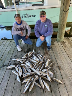 Larry Glynn and his friend Mike pose with their speckled trout catch during a recent fishing trip.