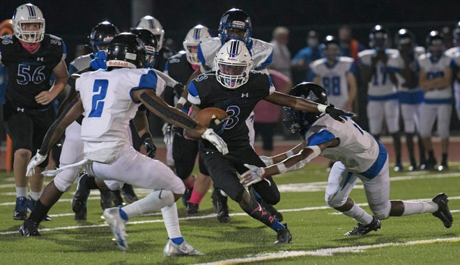 Mount Dora Christian Academy running back Matthew McKenzie (3) tries to dodge defenders in a game earlier this year against Wildwood at Bulldogs Stadium in Wildwood. [PAUL RYAN / CORRESPONDENT]