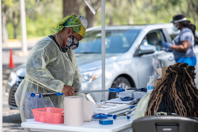 A health care worker packs COVID-19 while another conducts a test at Lake Sumter State College in Leesburg. [Cindy Peterson/Correspondent]