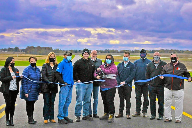 Amanda McGee, the manager of the Wayne County Aiport, cuts the ribbon for the new taxiway surrounded by (left to right) Wooster Area Chamber of Commerce President Samira Zimmerly, Wayne County Commissioners Becky Foster and Sue Smail, Airport Line Technician Matt Smucker, Airport Line Technician Dan Hodge, Commissioner Ron Amstutz, (McGee), Mark Heckroth of CHA Companies, Duane Dunn of CHA Companies, Dan Ford of CHA Companies, and county administrator Patrick Herron.