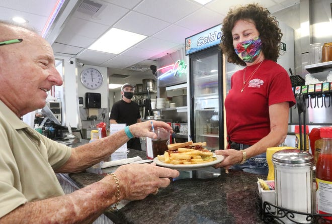 """Patti Fay, head waitress at the Starlite Diner in Daytona Beach, serves a customer's lunch at the counter. Fay voted for the constitutional amendment to gradually raise the state's minimum wage to $15 an hour. Although some in the hospitality and service industries say the wage increase will drive up prices for consumers, Fay thinks it's worth it. """"Any kind of help that can be given us is welcome,"""" she said of workers."""