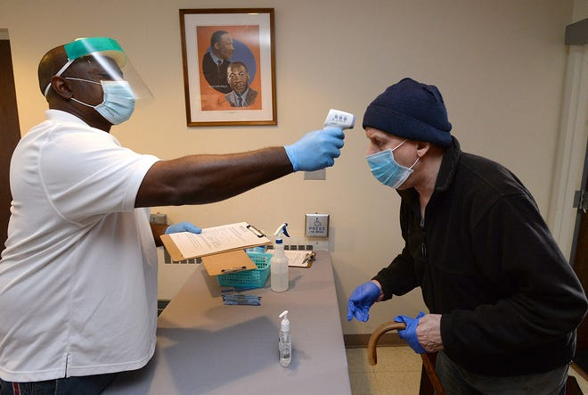 Brian Atterbury, left, a health worker with the Minority Community Investment Coalition, takes Erie resident Daniel Chapman's temperature Nov. 5 at the Martin Luther King Center during a free testing session.