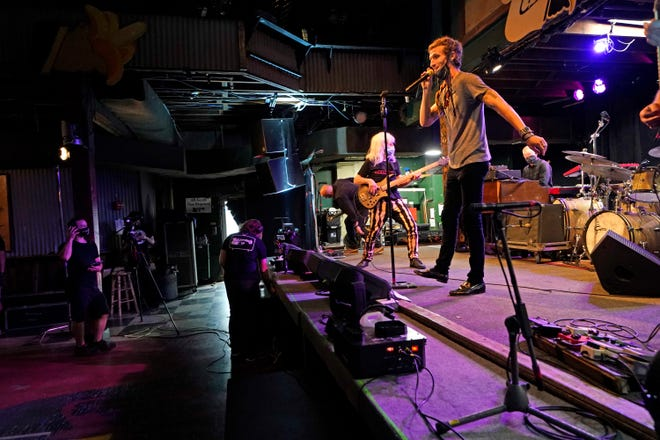 "In this Oct. 26, 2020, photo, David Shaw, foreground, frontman for the band The Revivalists, performs with actor Harry Shearer, co-author and character in the movie ""This Is Spinal Tap,"" as they record a video stream concert with the band Galactic, inside an empty Tipitina's music club, in New Orleans. Music clubs all over the nation are shuttered due to the coronavirus. And owners fear for the future of their businesses and of a musical way of life. (AP Photo/Gerald Herbert)"