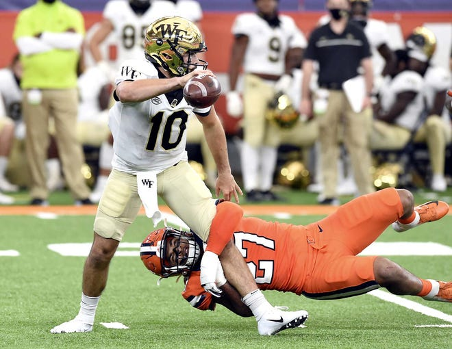 Syracuse linebacker Stefon Thompson (27) puts pressure on Wake Forest quarterback Sam Hartman (10) during Saturday's game in Syracuse, New York.